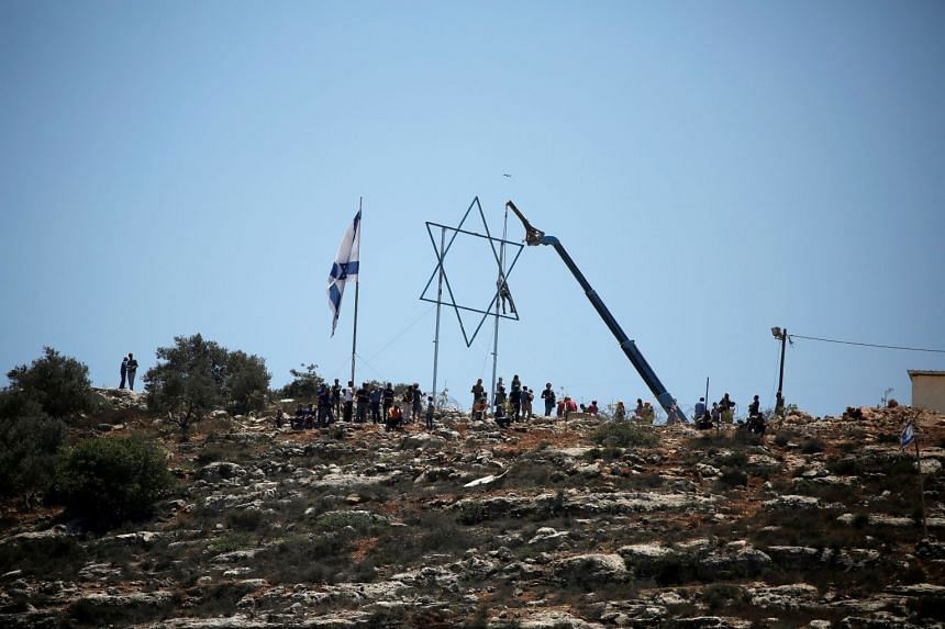 Israeli settlers erect poles with the Star of David in Evitar settlement during a protest by Palestinians against the settlements in Beita, in the Israeli-occupied West Bank on July 2, 2021
