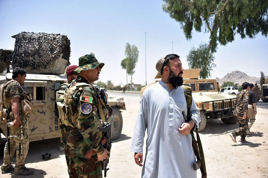 Afghan security personnel stand guard along the road in Kandahar, Afghanistan, on July 9, 2021.