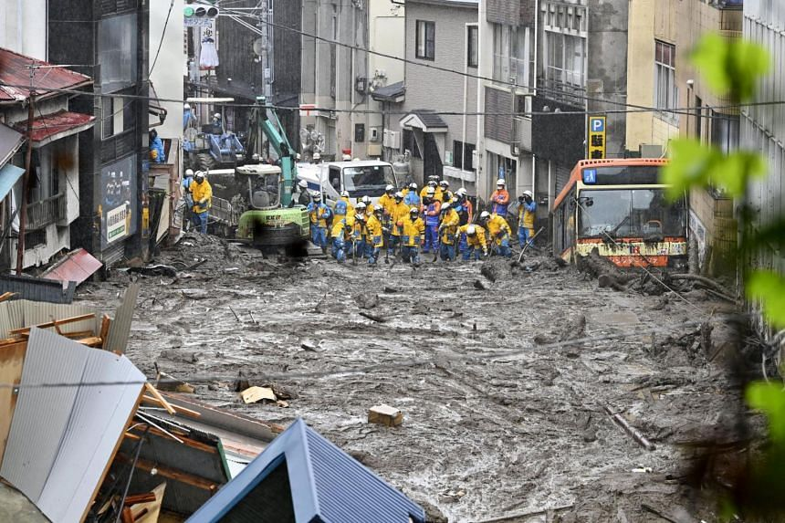 In a photo taken on July 4, 2021, police officers conduct a search and rescue operation at a mudslide site caused by heavy rain in Atami, west of Tokyo.