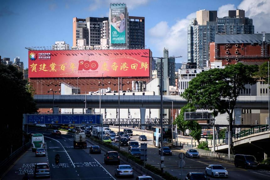 A billboard celebrating the 100th anniversary of the founding of the Communist Party of China displayed above a main road in Hong Kong.