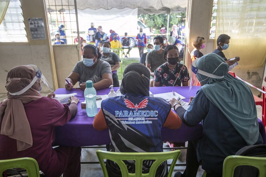 Volunteers assisting villagers in filling paperwork before Covid-19 vaccination in Banting, Malaysia, on July 8.