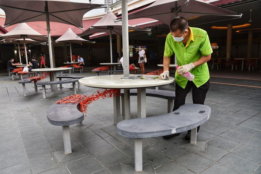 Cleaners removing tape with alcohol solution at Tiong Bahru Market, on July 11, 2021.