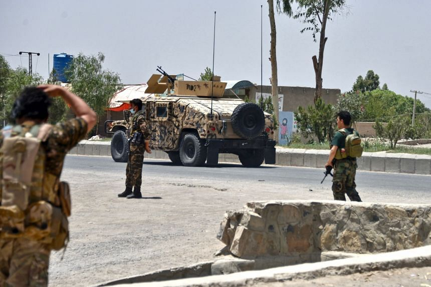 Afghan security personnel stand guard along the road amid ongoing fighting between Afghan security forces and the Taleban in Kandahar, on July 9, 2021.