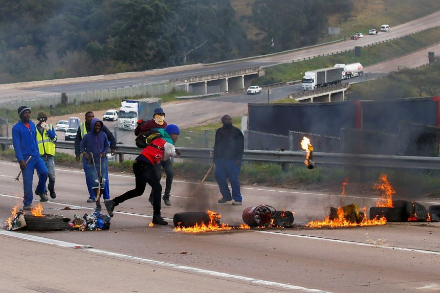 Supporters of former South African President Jacob Zuma block the freeway with burning tyres during a protest in Peacevale, on July 9, 2021.