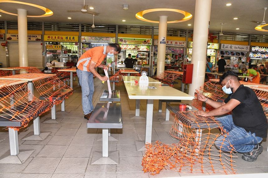 NEA contractors removing tape and plastic fencing from tables and chairs at Tiong Bahru Market, on July 11, 2021.