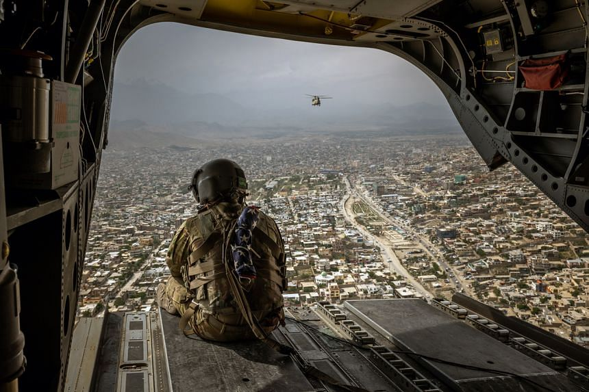 A photo from May 2, 2021, shows a US soldier on a CH-47 Chinook helicopter flying over Kabul, Afghanistan.