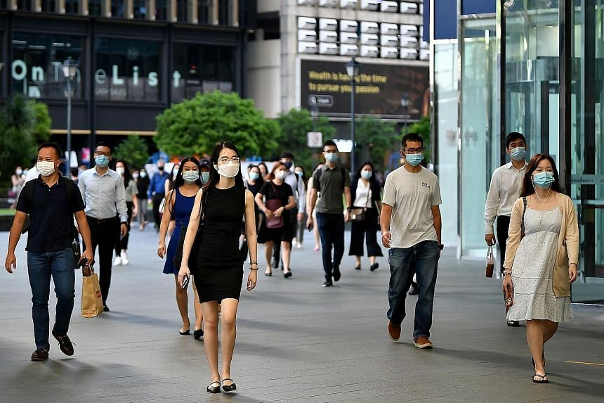 Office workers wearing face masks at Raffles Place in May. An uptick of Covid-19 cases that month led to tighter curbs, possibly putting a speed bump on the path to recovery for Singapore, said analysts.