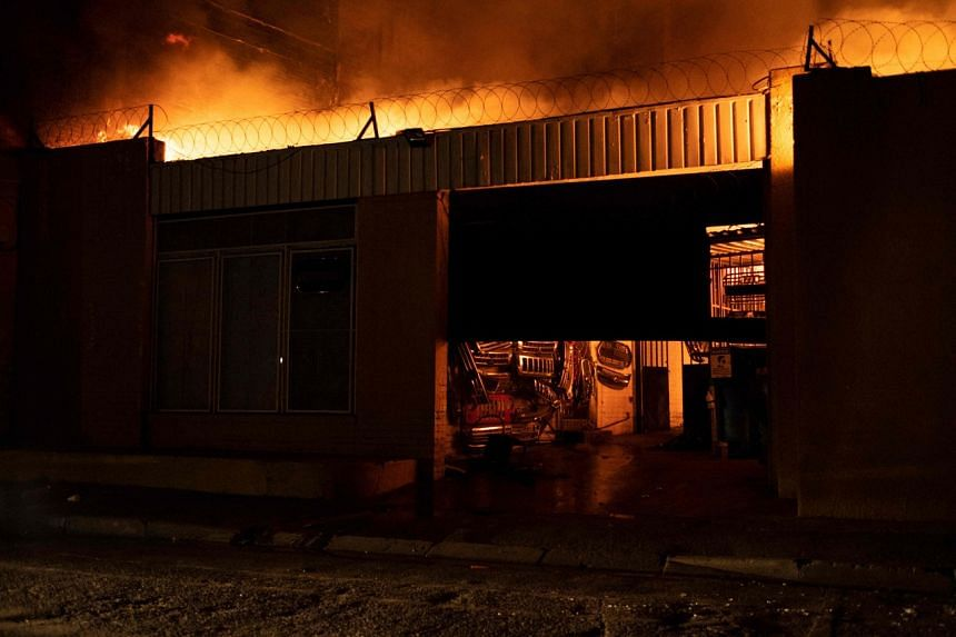 An auto spare parts shop burns during protests in Johannesburg, South Africa, on July 11, 2021.