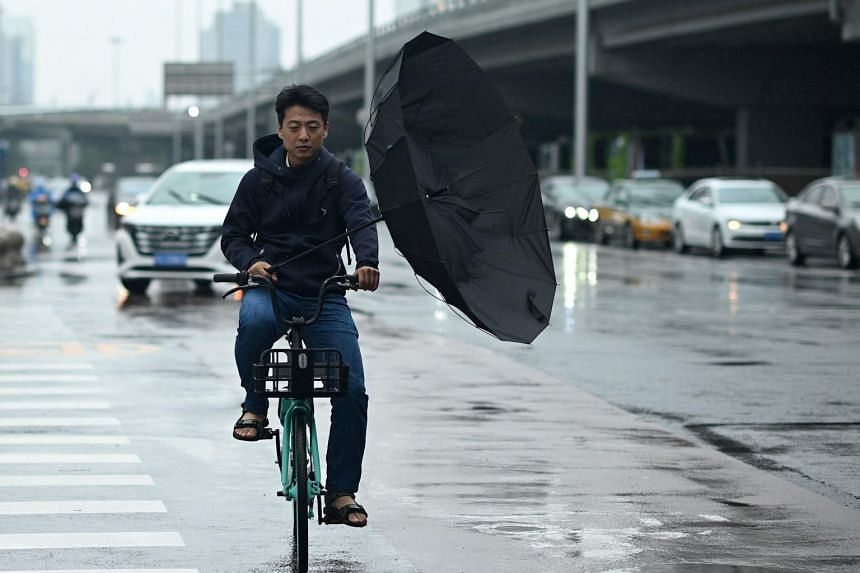 A man's umbrella is flipped as he pedals along a street in Beijing, on July 12, 2021.