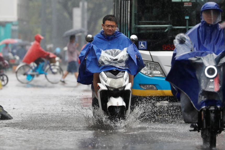 People wear raincoats as they ride electric scooters during a rainy day in Beijing, on July 12, 2021.