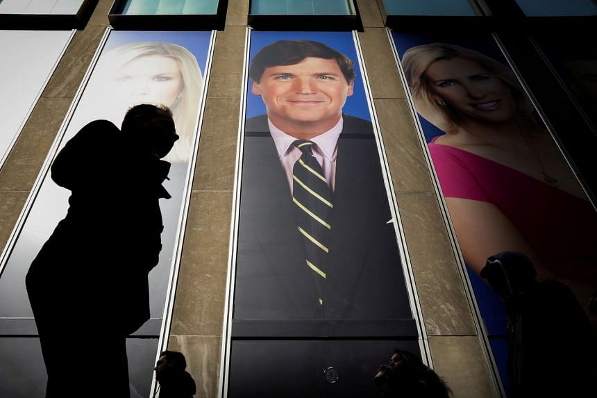 In a photo from March 13, 2019, people pass by a promo of Fox News host Tucker Carlson on the News Corporation building in New York.