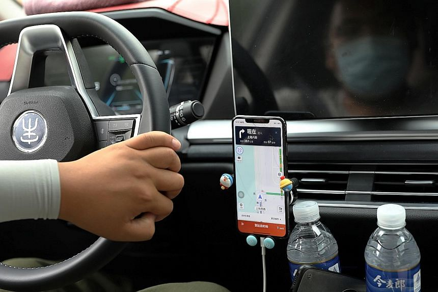 A driver of Chinese ride-hailing service Didi, with a phone showing a navigation map on Didi's app, in Beijing on July 5. A chill has settled over global finance after a fortnight in which China first cracked down on Didi within days of its US tradin