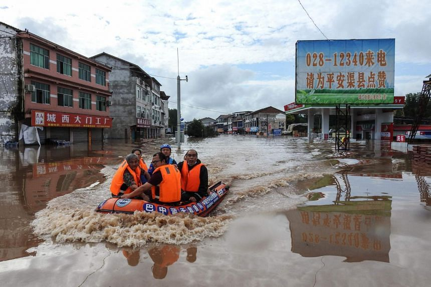 Rescuers evacuating residents from a flooded area following heavy rains in Dazhou, Sichuan, on July 11, 2021.
