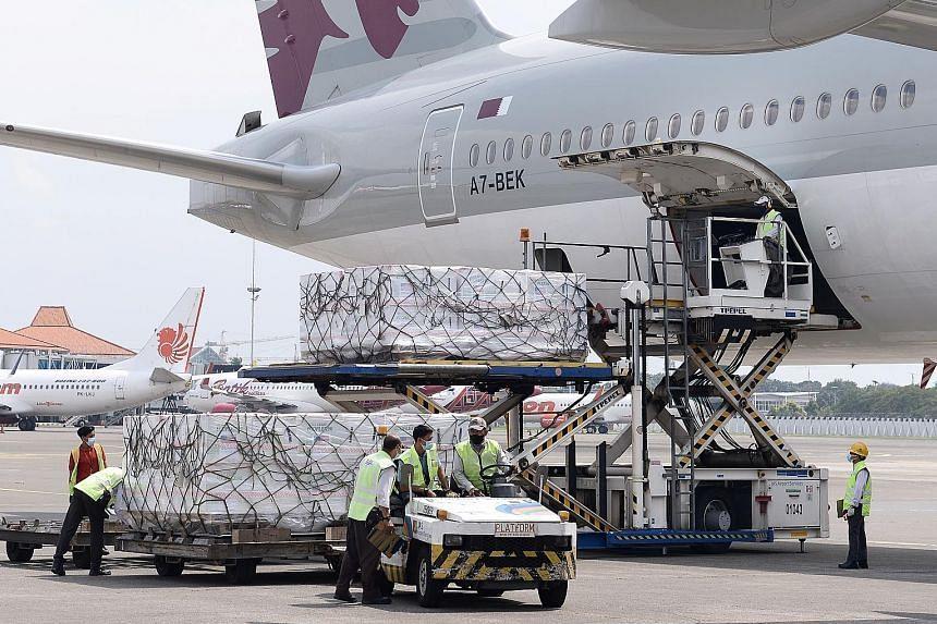 Workers at Indonesia's Soekarno Hatta International Airport in Tangerang unloading Moderna vaccines on July 11.