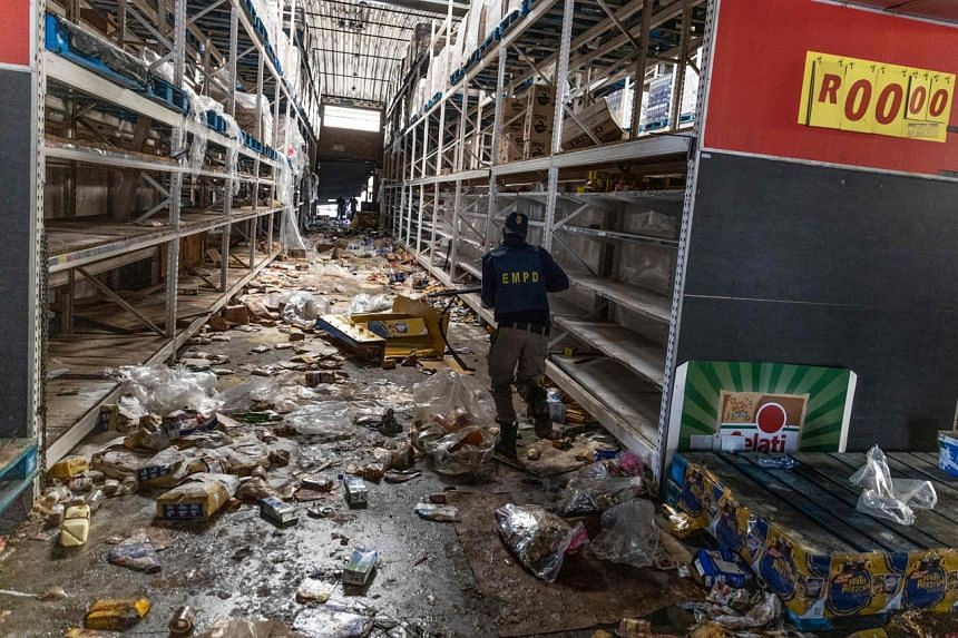 A member of the South African Police Services searches for looters inside the Gold Spot Shopping Centre in Vosloorus, Johannesburg, on July 12, 2021.