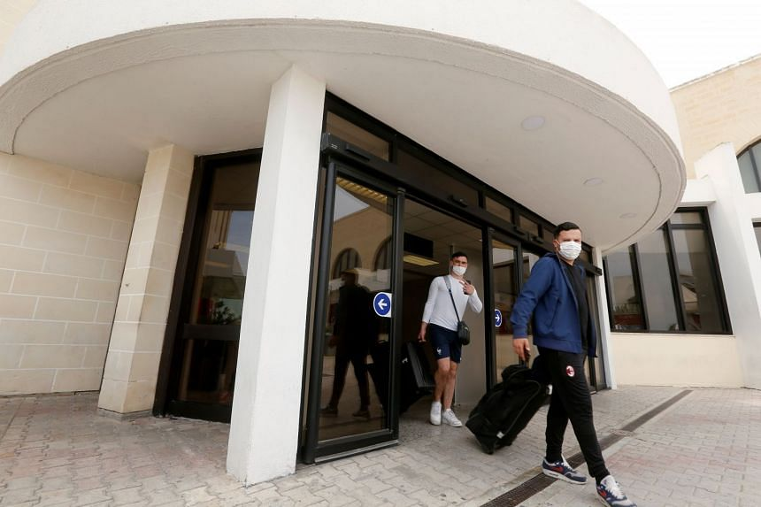 Tourists walk out of the terminal building at Malta's international airport after arriving on June 1, 2021.