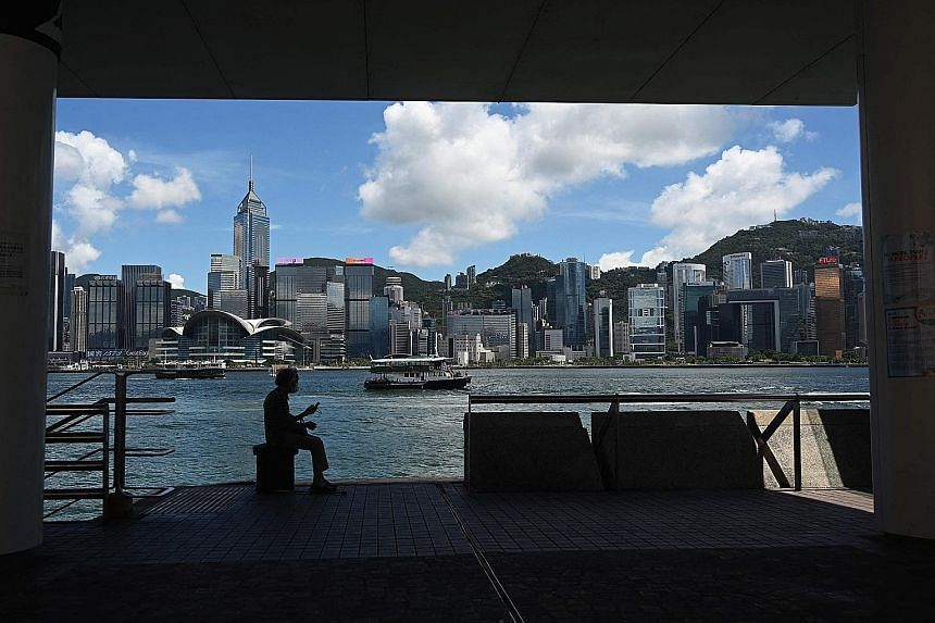 A woman listening to her portable radio at the waterfront of Hong Kong's Victoria Harbour yesterday. With the more transmissible Delta variant behind the rise in cases in a number of countries, Hong Kong is not primed to reopen its borders, given its