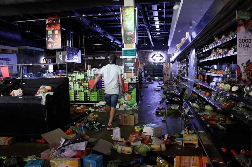 A man looking for looters inside a supermarket in Durban, South Africa, on July 13, 2021.