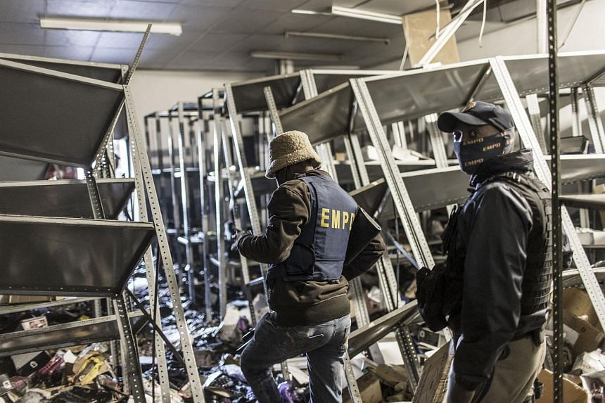 Police officers examining a looted store at a mall in Vosloorus, on July 13, 2021.