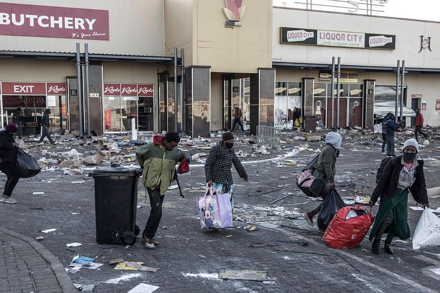 Looters carrying items they took from a vandalised mall in Vosloorus, South Africa, on July 14, 2021.