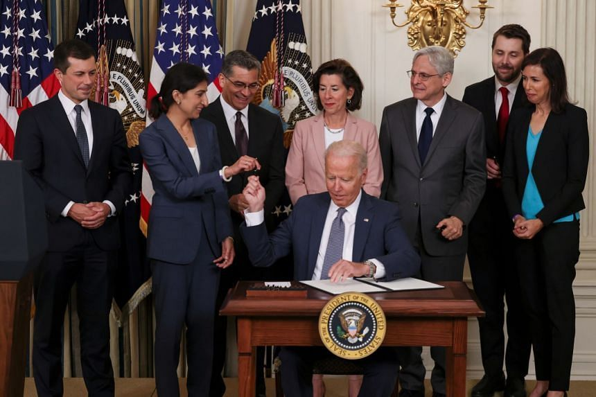 """US President Joe Biden signs an executive order on """"promoting competition in the American economy"""" as members of his Cabinet stand by at the White House."""