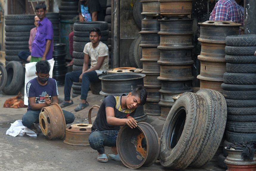 A youth cleans rusts from a car wheels at a workshop in Dhaka on June 8, 2021.