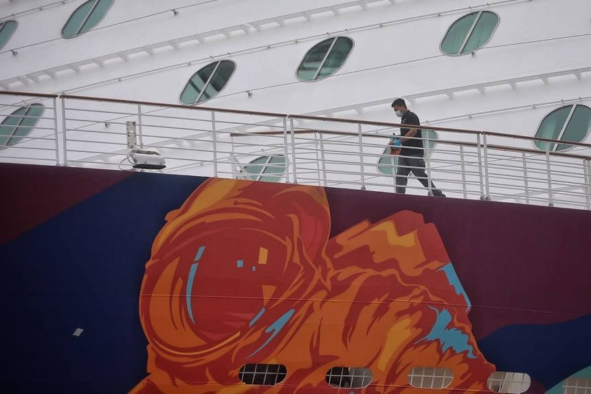 A staff is seen with disinfectant on Dream Cruises' World Dream docked at Marina Bay Cruise Centre on July 14, 2021.