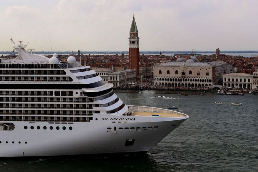 Tugboats escort the MSC Orchestra cruise ship across the basin past the Bell Tower and the Doge's palace as it leaves Venice on June 5, 2021.
