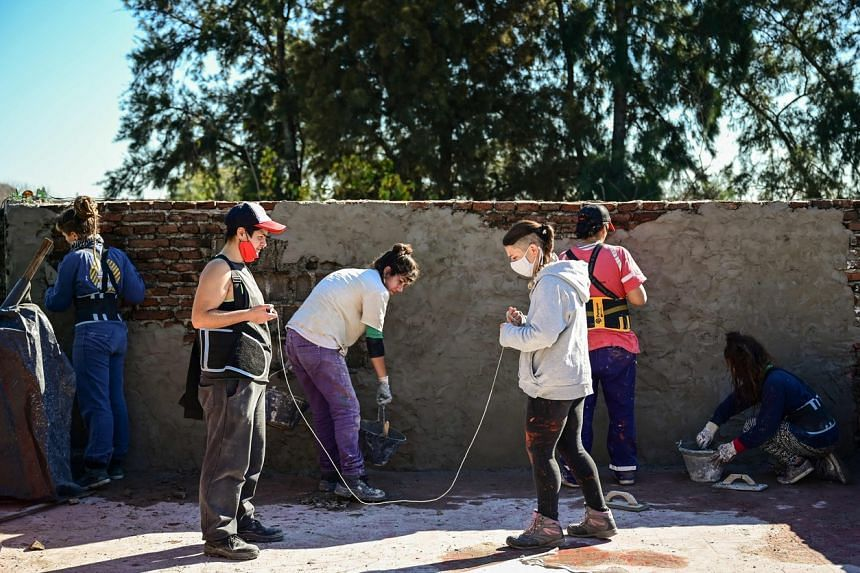 Female bricklayers work in the construction of a house in Lanus, Buenos Aires, on June 22, 2021.