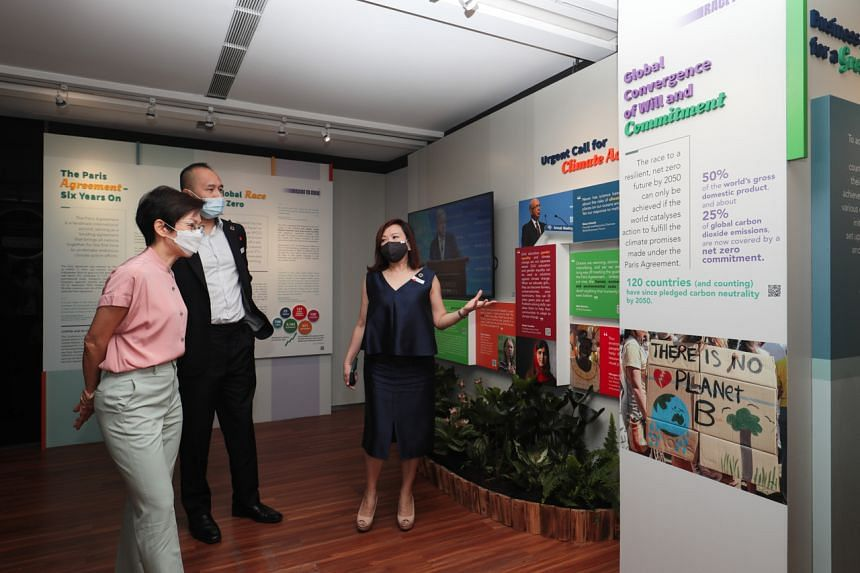 """(From left) Minister for Sustainability and the Environment Grace Fu, CDL Group chief executive Sherman Kwek and Ms Esther An tour the """"Change the Present, Save the Future"""" exhibition, on July 14, 2021."""