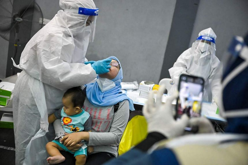 A medical worker administers a Covid-19 test at a testing site in Shah Alam on May 27, 2021.