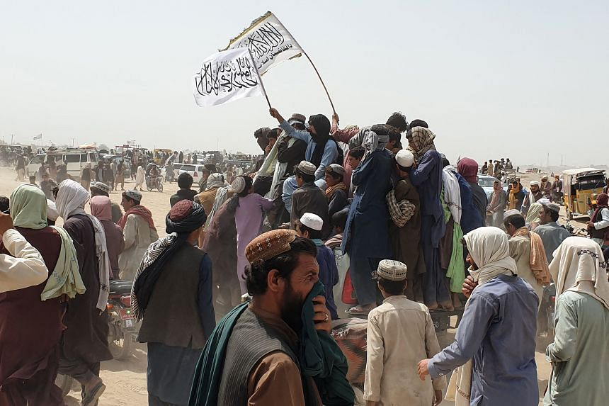 People wave Taleban flags as they drive through the Pakistani border town of Chaman on July 14, 2021.