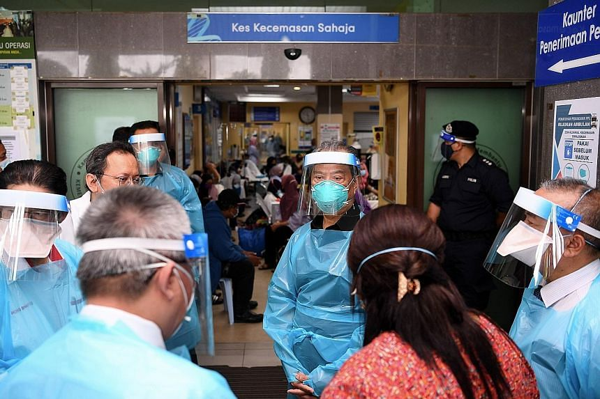 Prime Minister Muhyiddin Yassin (facing camera) visiting a hospital emergency ward treating Covid-19 patients in Klang, Selangor, on Tuesday.