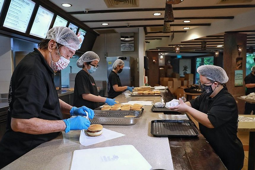 Service staff wrapping burgers at The Social Kitchen's Jurong Bird Park branch on July 14, 2021. Ms Jessica Szeto (right), who has Down syndrome, was hired last November.