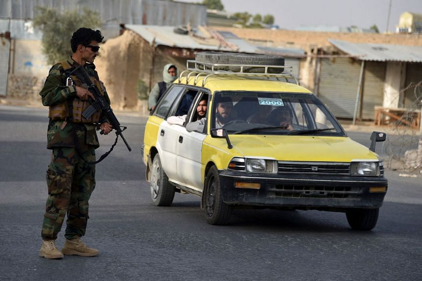 An Afghan security officer stands guard along a road in Kandahar on July 14, 2021.