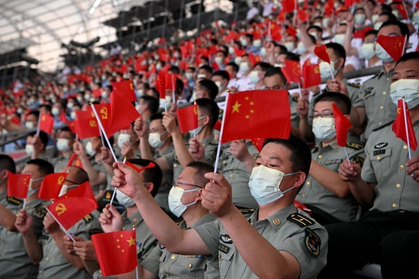 Chinese citizens wave national flags during the celebration of the 100th Anniversary of the founding of China's Communist Party in Beijing, on June 28, 2021.