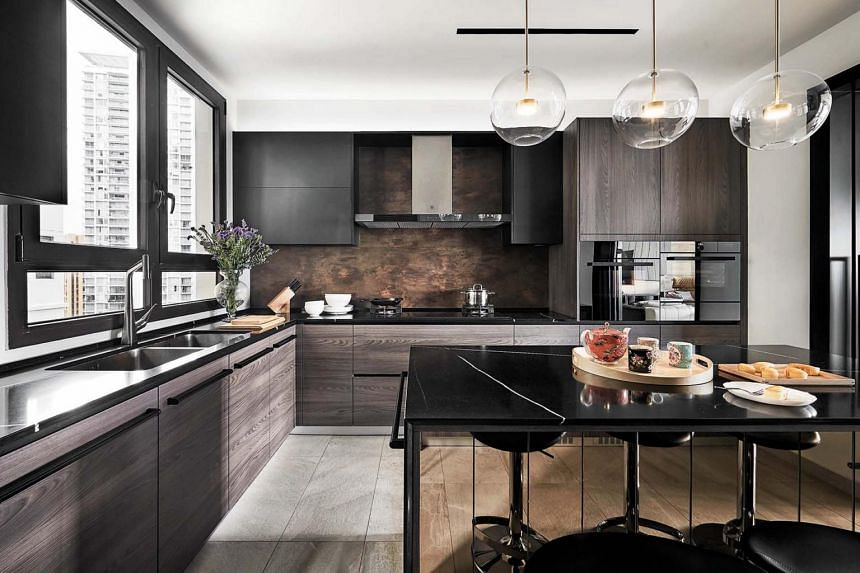A trio of glass pendant lamps and the bronze mirror backing of the island add luxe to the kitchen.