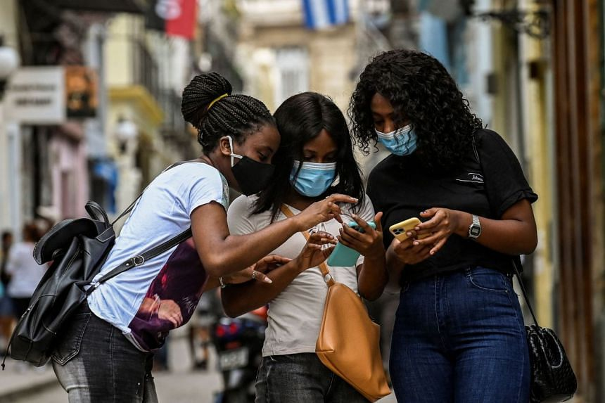 Women use their phones in a Havana street on July 14, 2021