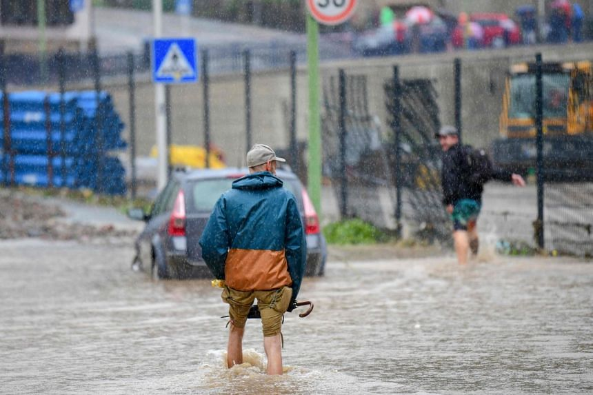 Two men wading through the water of a flooded street in Hagen, western Germany, on July 14, 2021.