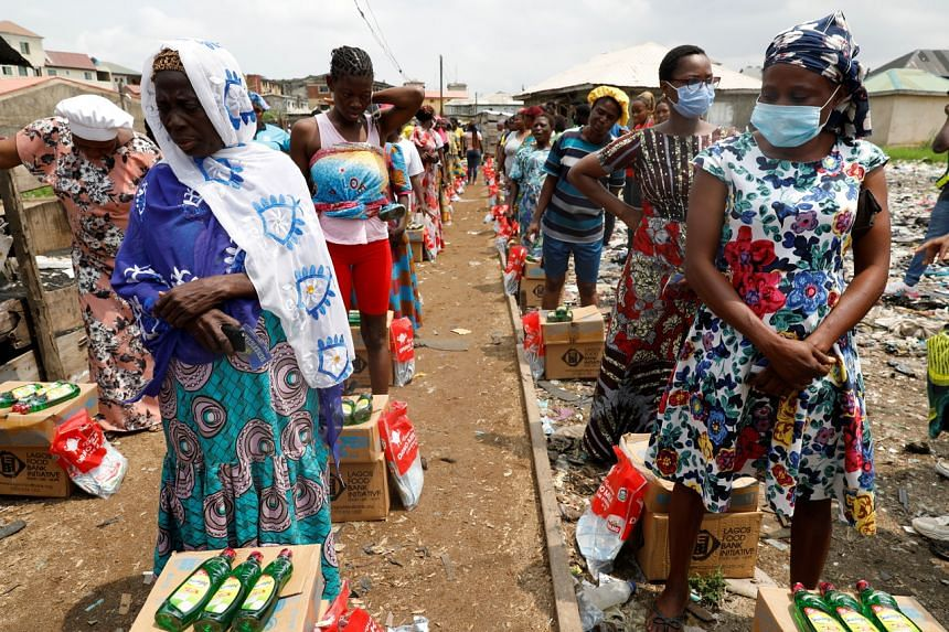 Women queue for food parcels during distribution by volunteers of the Lagos food bank initiative in a community in Oworoshoki, Lagos, on July 10, 2021.