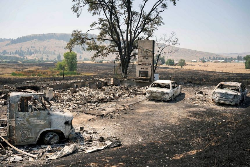 Burned vehicles sit outside a home destroyed by the Chuweah Creek Fire as wildfires devastate Nespelem in eastern Washington state, on July 15, 2021.