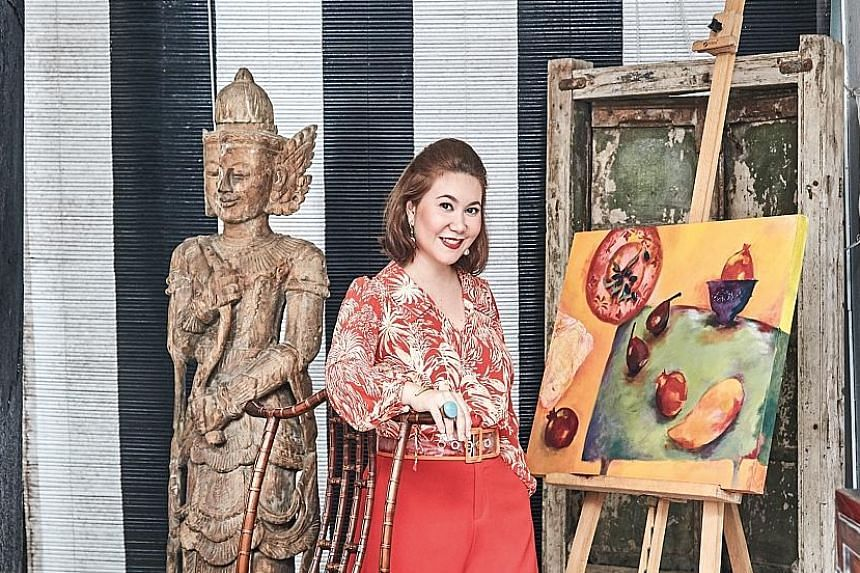 (Above) Ms Malissa Desmazieres with one of her own artworks in the dining corner of her patio, which is decorated with an old Indian window and a Burmese statue. (Left) The indoor living room features a 20th-century Japanese screen, Thai lacquered ca