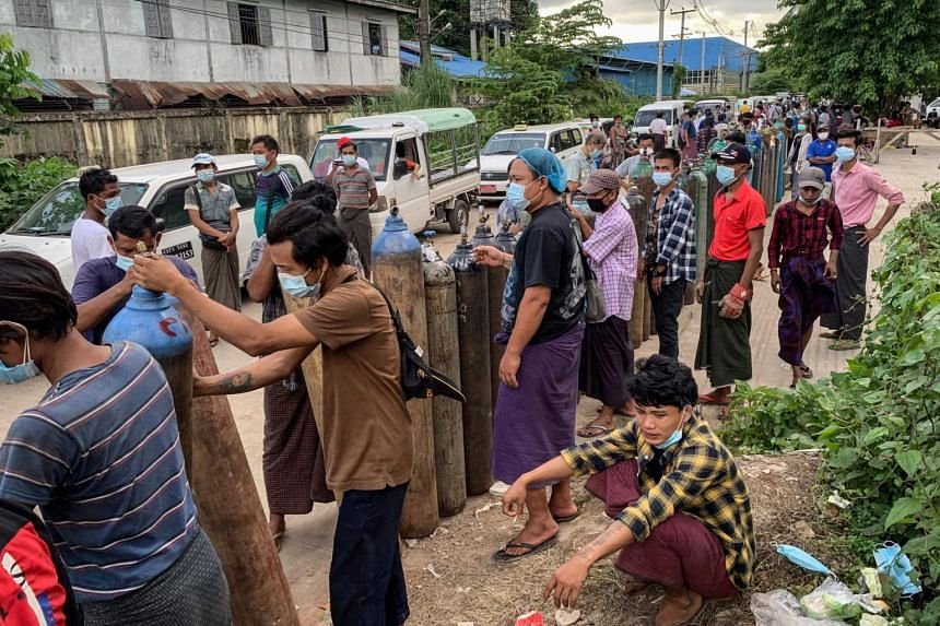 People waiting to fill up empty oxygen canisters outside a factory in Yangon on July 14, 2021.