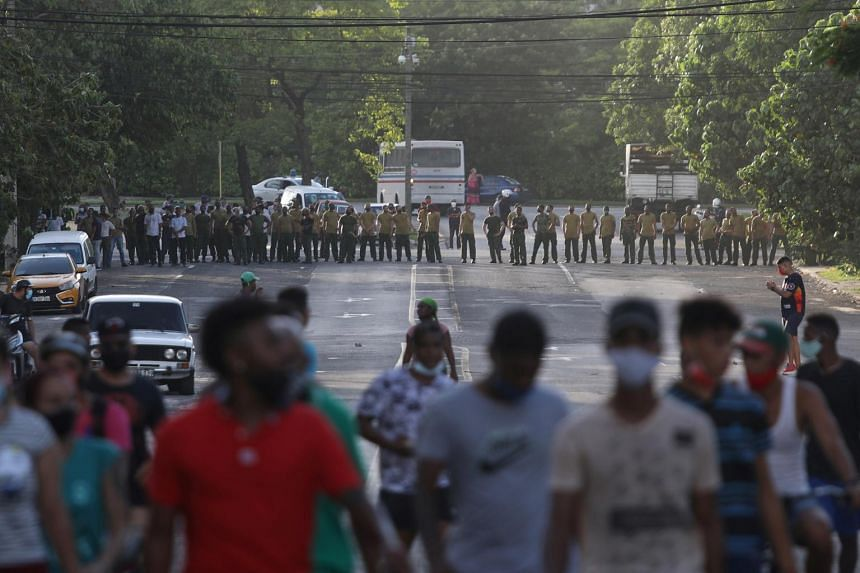 Demonstrators walk away from army soldiers blocking a road during a protest in Havana, on July 11, 2021.