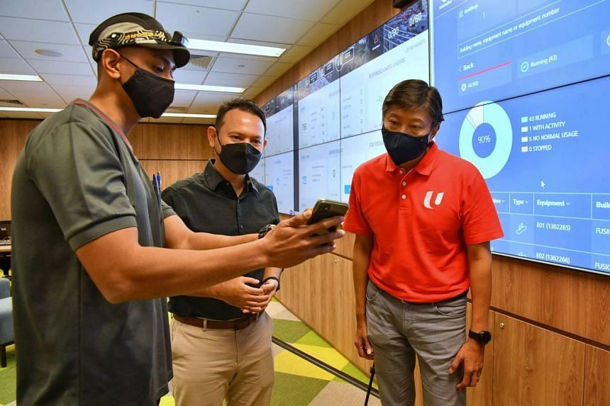 NTUC secretary-general Ng Chee Meng (in red shirt) and Senior Minister of State for Manpower Zaqy Mohamad being shown a workflow app on the phone of Schindler Lifts technician Abdul Razak Abd Rahman on July 16, 2021.