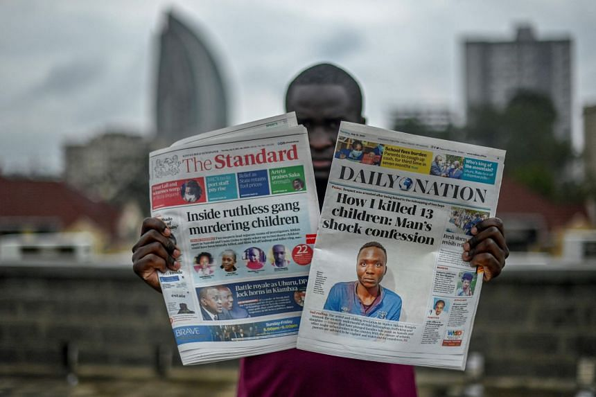 A man holds up Kenyan daily newspapers featuring the case in Nairobi on July 15, 2021.
