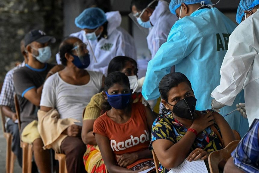 Army health officials inoculate people against coronavirus at a vaccination site in Sri Lanka on July 15, 2021.