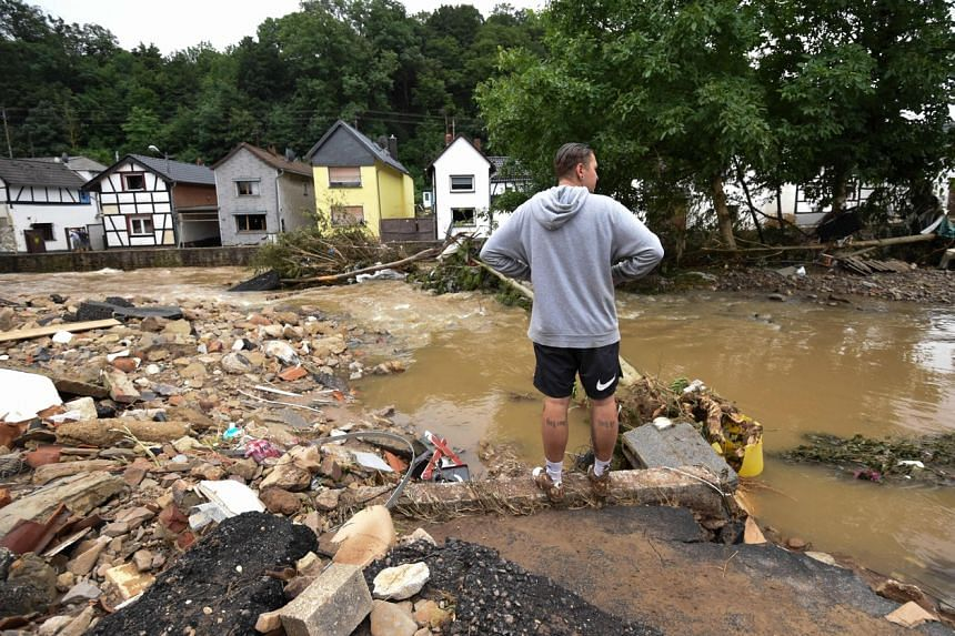 A man standing at a flooded intersection near the Erft river in Iversheim near Bad Muenstereifel, Germany, on July 16, 2021.