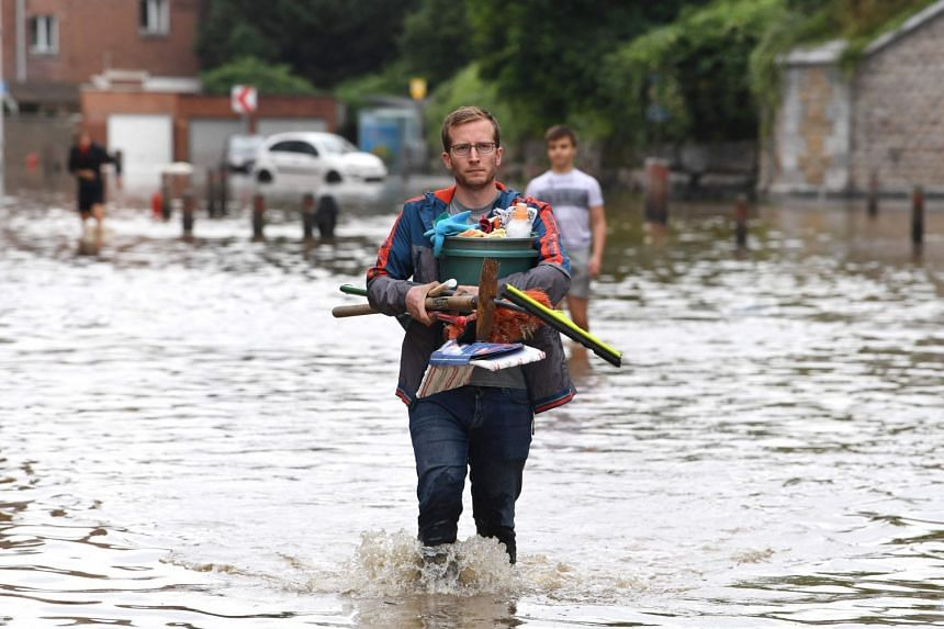 A local resident walks in a flooded street in Angleur, near Liege, on July 16, 2021.