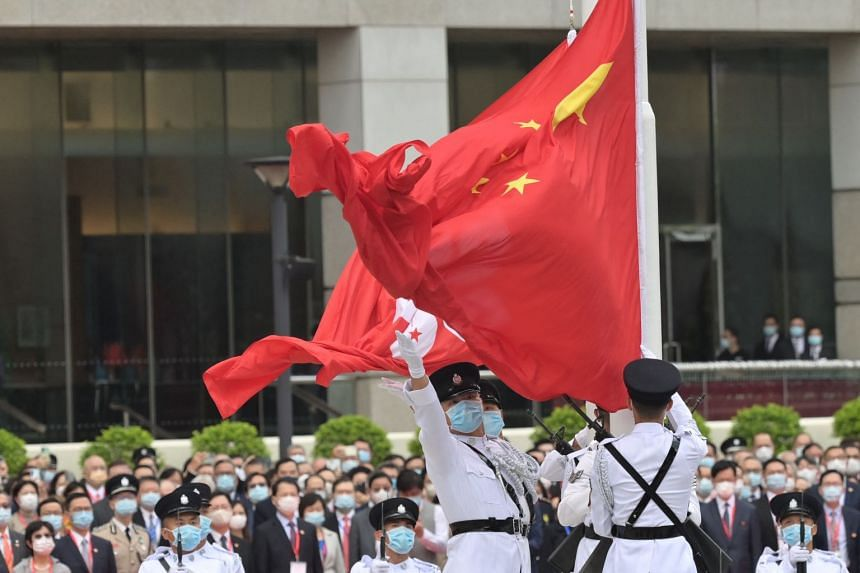 The Chinese (front) and Hong Kong flags are raised during a ceremony to mark the 24th anniversary of Hong Kong's handover from Britain, in Hong Kong on July 1, 2021.